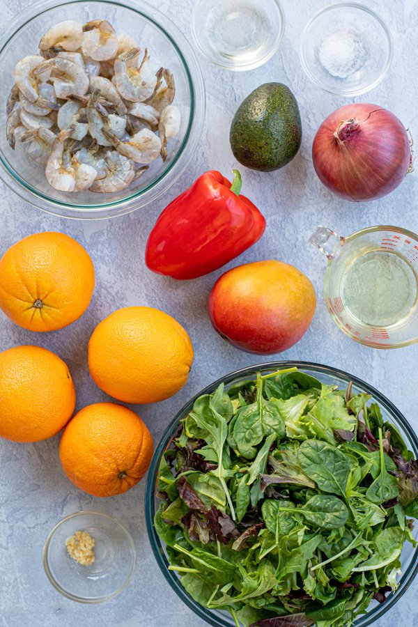 All of the ingredients needed for Shrimp Salad with Avocados and Oranges sitting on a tabletop.