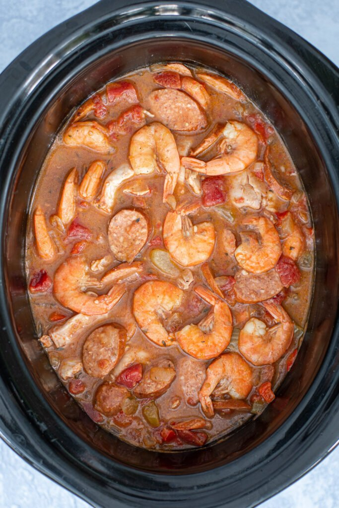 Overhead view of a crockpot filled with cook gumbo including cooked shrimp on the top.