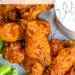 Pinterest Pin with text overlay 'Instant Pot Hot Wings'. Image of platter with pile of saucy chicken wings next to dipping sauce.