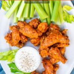 Pinterest Pin with text overlay 'Pressure Cooker Hot Wings'. Image of platter with pile of saucy chicken wings next to dipping sauce.