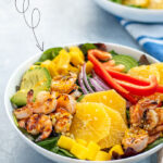 Pinterest Pin with text overlay 'Shrimp Salad with Orange Vinaigrette'. Image of large bowl filled with mixed greens, grilled shrimp, avocado, and oranges.