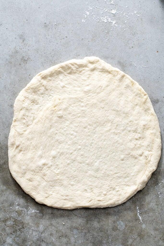 Pizza dough shaped into a circle.