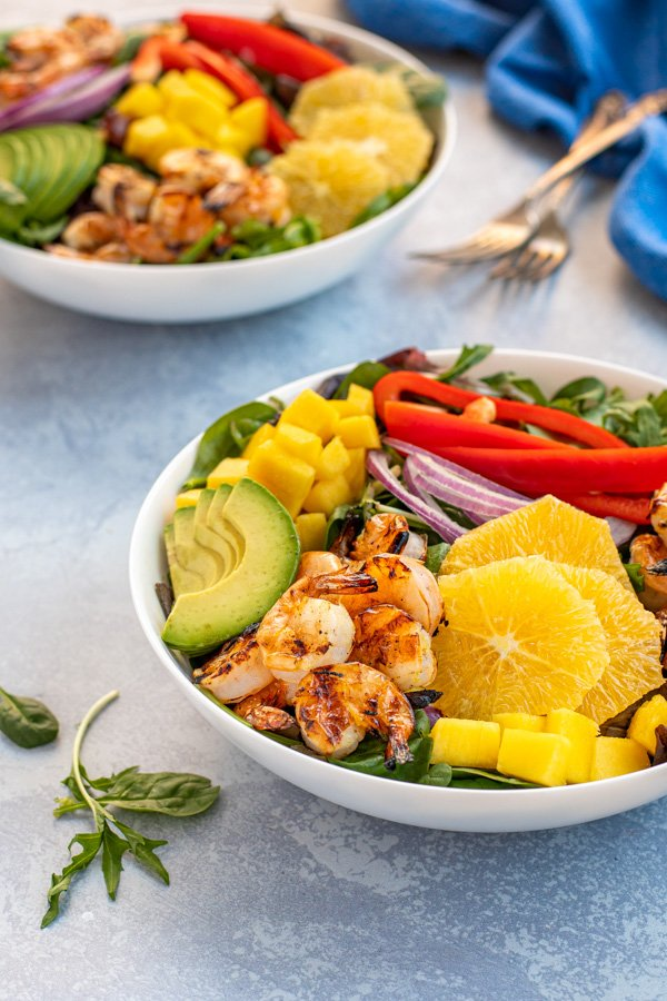 Two large bowls of grilled shrimp on green lettuce with avocados, oranges, mango, and bell pepper.