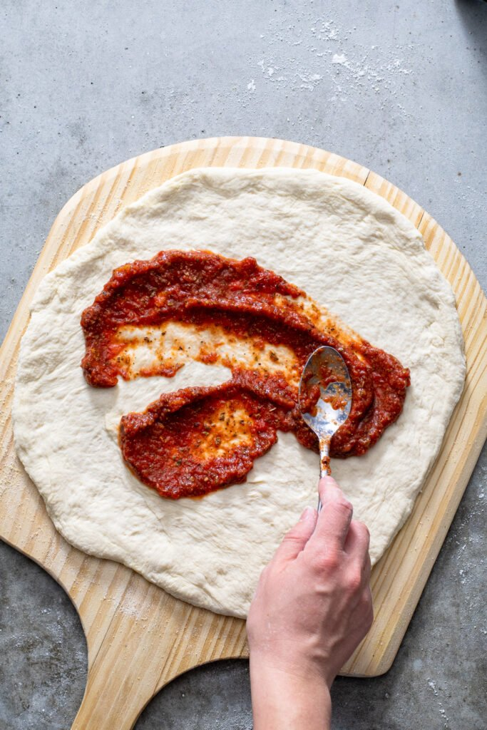 Spoon spreading 5 minute pizza sauce all over pizza dough.