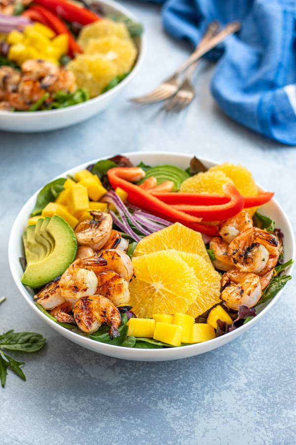 A large white bowl on a table with mixed greens topped with grilled shrimp, avocado slices, oranges, and diced mango.
