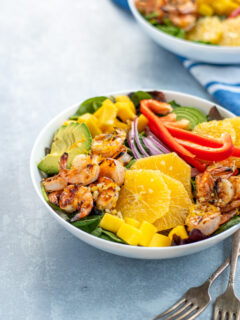 A large white bowl filled with mixed greens topped with grilled shrimp, avocado, oranges, mangos, red bell pepper, and red onions.
