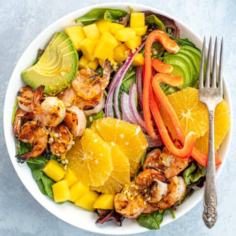 Overhead photo of a large white bowl filled with mixed greens with grilled shrimp, avocado, oranges, and mangos.