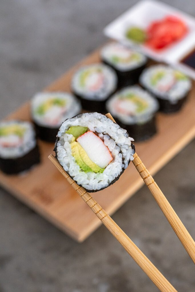 A pair of chopsticks holding up a California roll showing off the insides of crab, cucumber, and avocado.