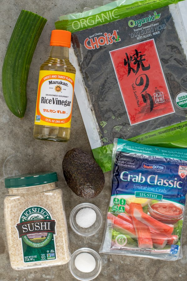 All the ingredients needed to make California roll Sushi sitting on a counter top.