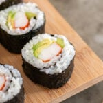 Pinterest Pin with text overlay 'Easy to make California Sushi Rolls', images of sushi on a serving platter.