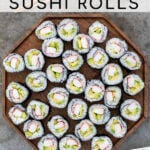 Pinterest Pin with text overlay 'Homemade California Sushi Rolls', image of large wood platter filled with sushi rolls.