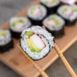 Pinterest Pin with text overlay 'California Sushi Rolls', image of sushi roll being held by chopsticks.