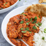 Pinterest Pin with text overlay 'Chicken Tikka Masala made with no heavy cream', image of bowl of chicken tikka masala next to a bed of rice.