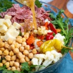 Pinterest Pin with text over lay 'Antipasto Salad with easy oregano dressing', image of a bowl of arugula topped with the ingredients of the salad with dressing being poured on.