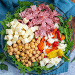 Pinterest Pin with text over lay 'Antipasto Salad with easy oregano dressing', image of a bowl of arugula topped with the ingredients of the salad.