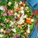 Pinterest Pin with text over lay 'Easy to Make Antipasto Salad', image of a bowl of arugula topped with the ingredients of the salad.