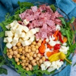 Pinterest Pin with text over lay 'Antipasto Salad', image of a bowl of arugula topped with the ingredients of the salad.
