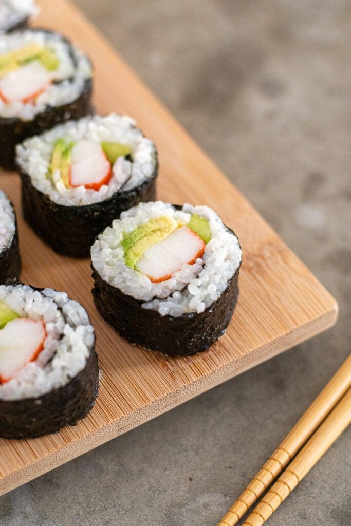 Platter of California rolls next to chopsticks.