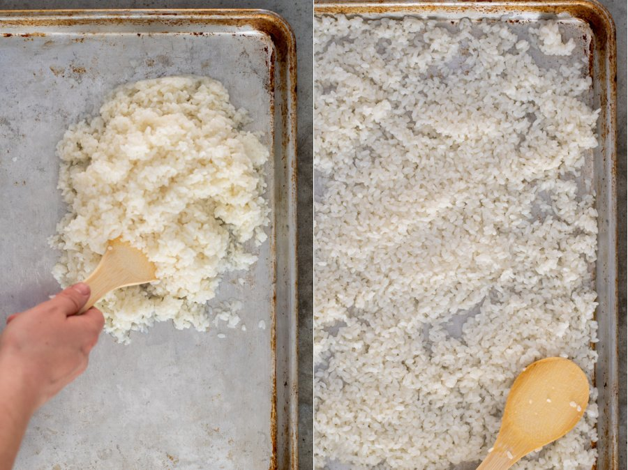 Tossing sushi rice on a tray with with vinegar and then spreading out on the pan to cool down.