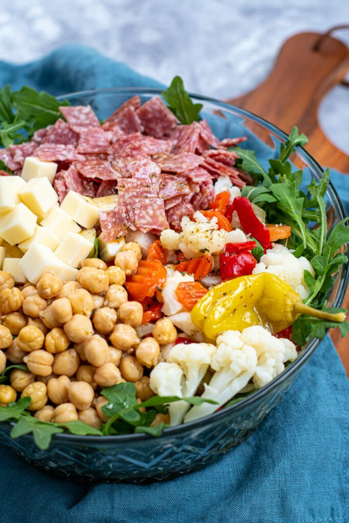 Dressed topping over a bed of arugula make up this easy antipasto salad.