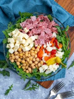 Overhead view of a glass bowl with the toppings for easy antipasto salad laid out evenly over a bed of arugula lettuce.