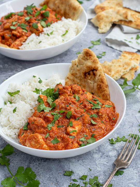 Chicken Tikka Masala is a large white bowl next to a scoop of rice and with a torn piece of naan.
