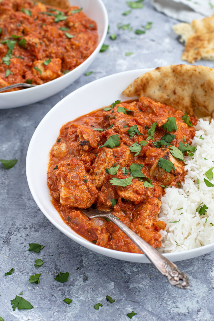 A fork in a large white bowl of chicken tikka masala next to a large scoop of rice and sprinkled with cilantro.
