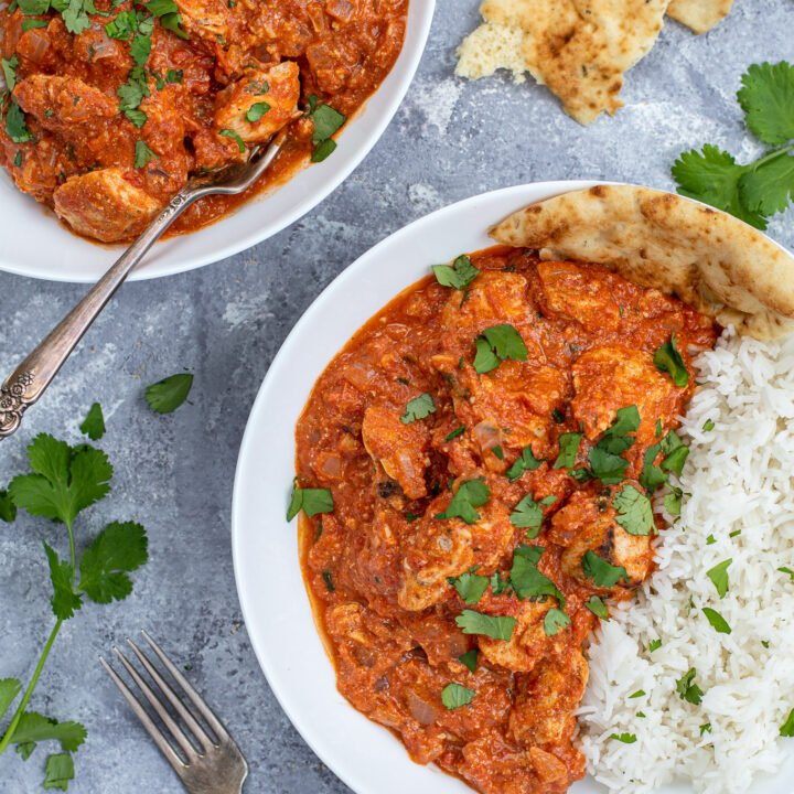 Overhead close up of chicken tikka masala in a large white bowl next to a bed of rice covered with sprinkles of cilantro.