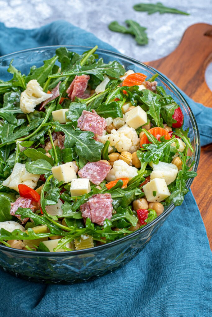 A tossed easy antipasto salad in a glass salad bowl showing off cheese cubes, salami, and pickled vegetables.