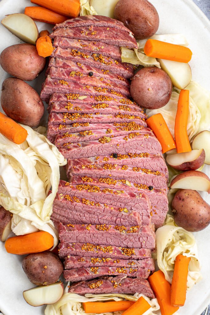 Freshly cooked and cut corned beef laid out on a cream platter with cabbage and carrots.