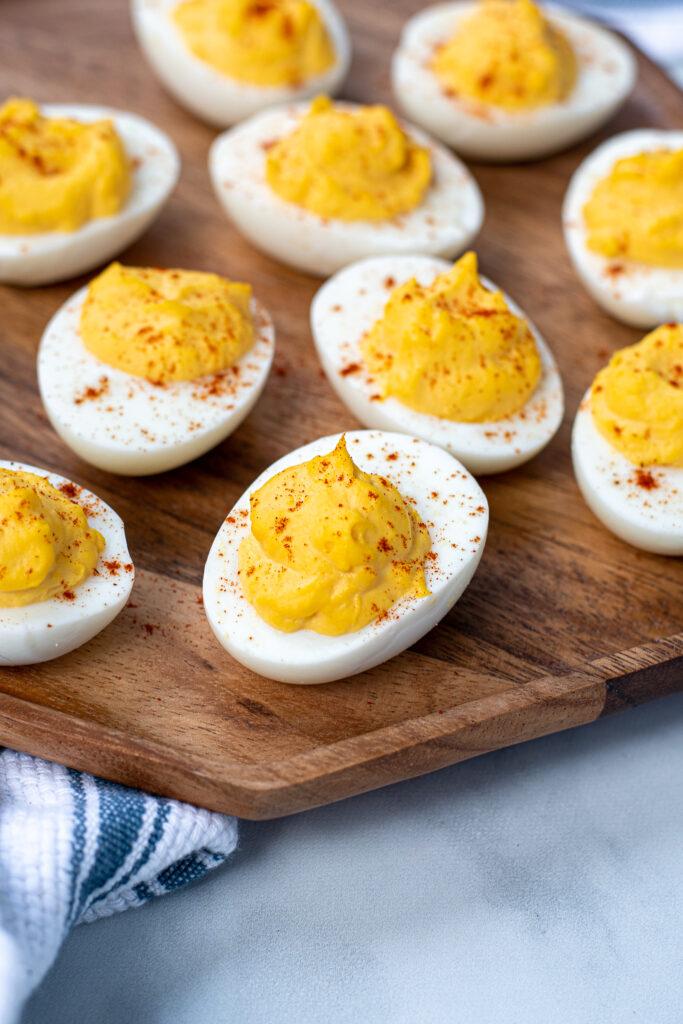 Close up of a deviled egg on a platter showing off the paprika garnish.