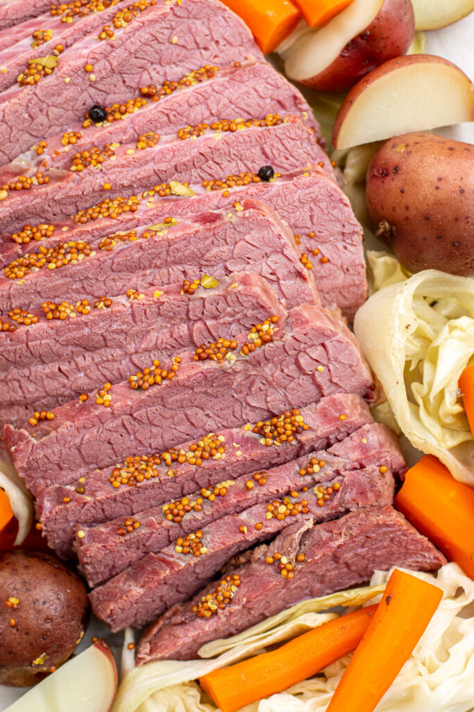 Close up of the cooked corned beef in slices topped with whole grain mustard.