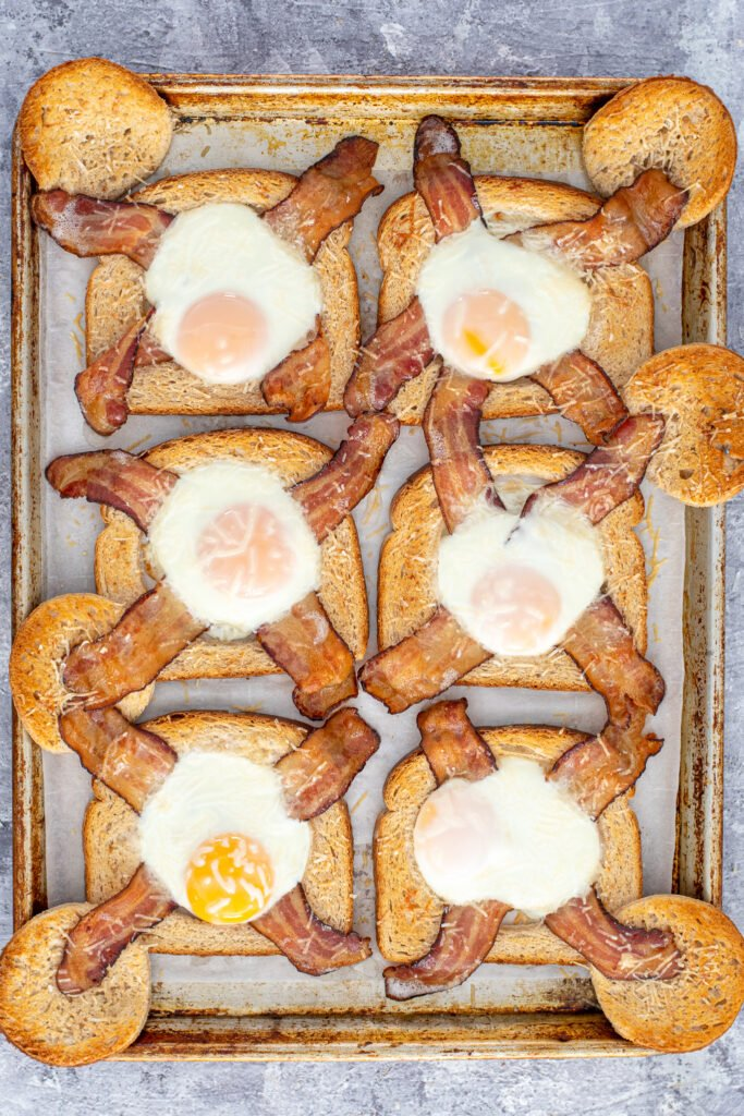 Cooked sheet pan egg in a hole fresh out of the even with golden toast and set eggs.