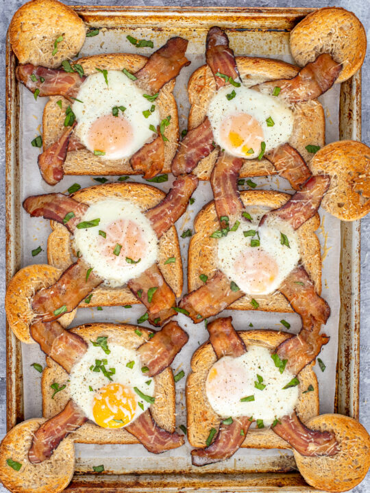 A sheet pan full of freshly baked egg in a hole with bacon garnished with sprinkled greens.