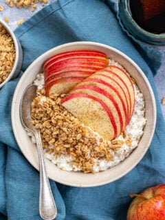 A white bowl on a blue towel filled with cottage cheese and apples with granola and ground cinnamon with a spoon ready to eat.