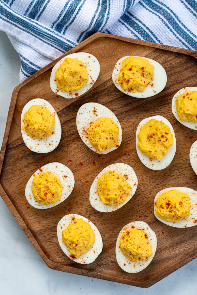 Wooden platter filled with many easy deviled eggs, garnished with sprinkles of red paprika.