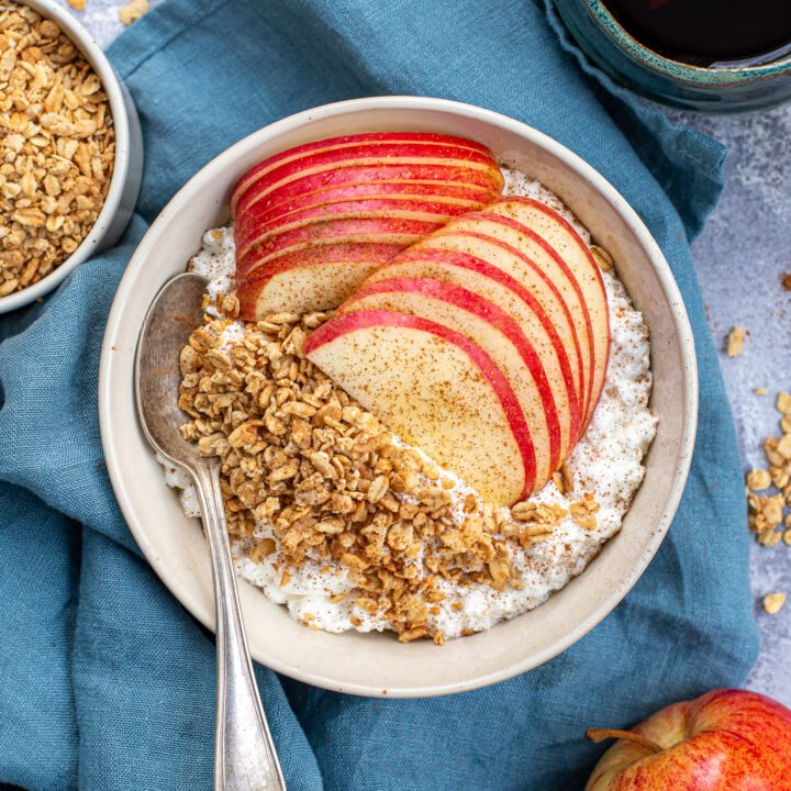 Overhead view of a breakfast table with a bowl full of cottage cheese and apple with granola and cinnamon.