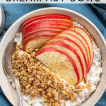 Pinterest Pin with text 'Apple Cinnamon Cottage Cheese Breakfast bowl', image of a bowl on a blue towel filled with cottage cheese, apple slices, and granola.