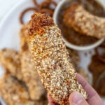 Pinterest Pin with text 'Pretzel Crusted Chicken Tenders', image of stack of chicken tenders on a plate next to honey mustard.