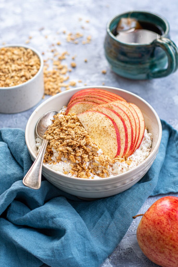 A bowl on a blue towel, the bowl is filled with cottage cheese and topped with apple slices, granola, and dusted in cinnamon.