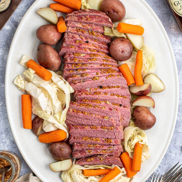 Sliced Corned Beef and a large platter next to sliced cabbage, carrots, and potatoes.