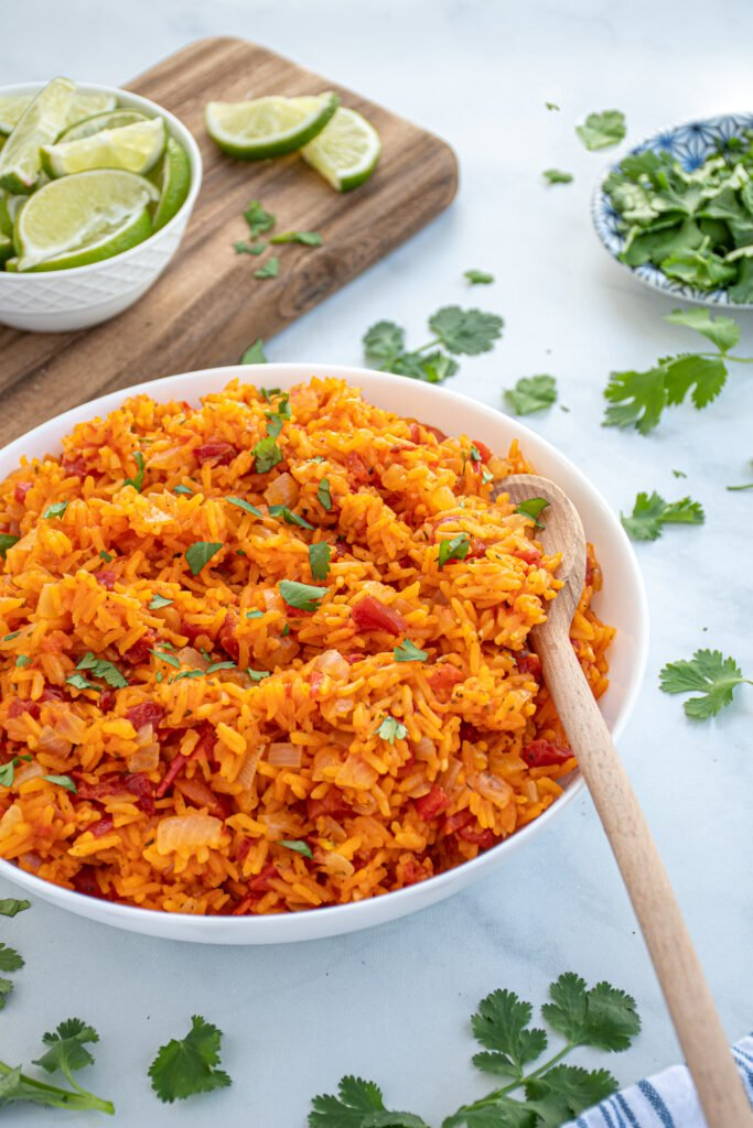 Large white bowl filled with red-orange colored mexican rice garnished with cilantro with a wooden spoon.