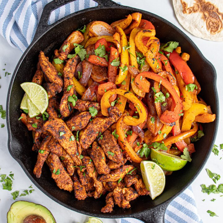 A large cast iron skillet filled with charred chicken fajitas and bright peppers.