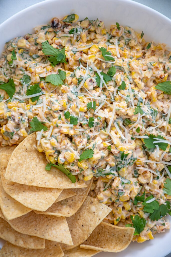 Close up view on corn, parmesan cheese, and cilantro in a a quick and easy corn dip recipe.