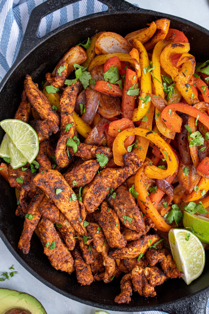 Close up of chicken fajitas in a cast iron next to colorful bell peppers.