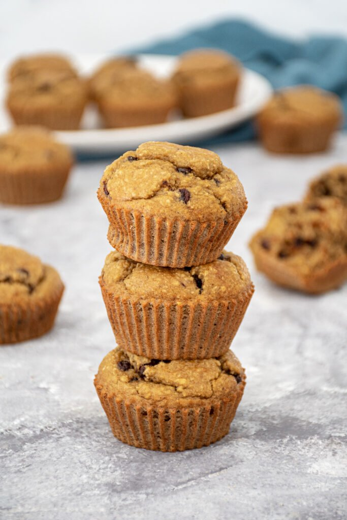 A stack of 3 blender flourless banana muffins with mini chocolate chips making a muffin tower with a plate of muffins in the background.