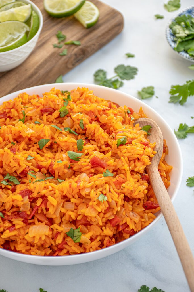 Bright orange-red colored Mexican Rice in a large white bowl with a wooden spoon garnished with chopped cilantro.