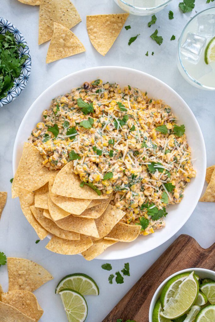 Large what bowl filled with Mexican Street Corn Dip and tortilla chips surrounded by more chips, cilantro, and limes.