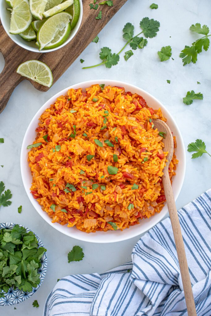 Overhead view of a large white bowl of mexican rice on a table surrounded by cilantro and cut up limes.