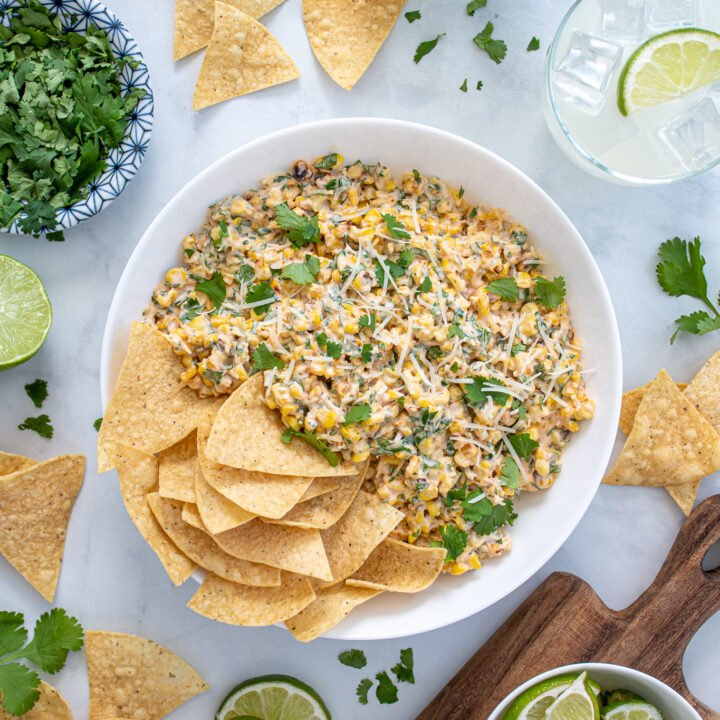 Overhead view of a table scene with a large bowl of Mexican street corn dip with tortilla chips surrounded by cut limes, cilantro pieces, and margaritas.
